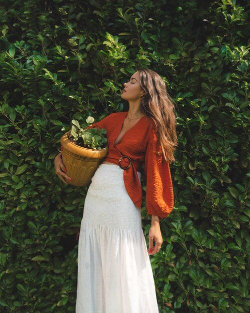 a boho summer outfit with an orange cropped blouse with puff sleeves and a white midi skirt is cool and relaxed