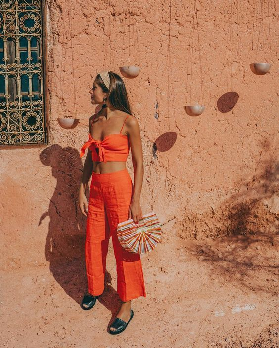 a bold orange set with trousers and a cropped tied up top, navy slippers, a bright bag