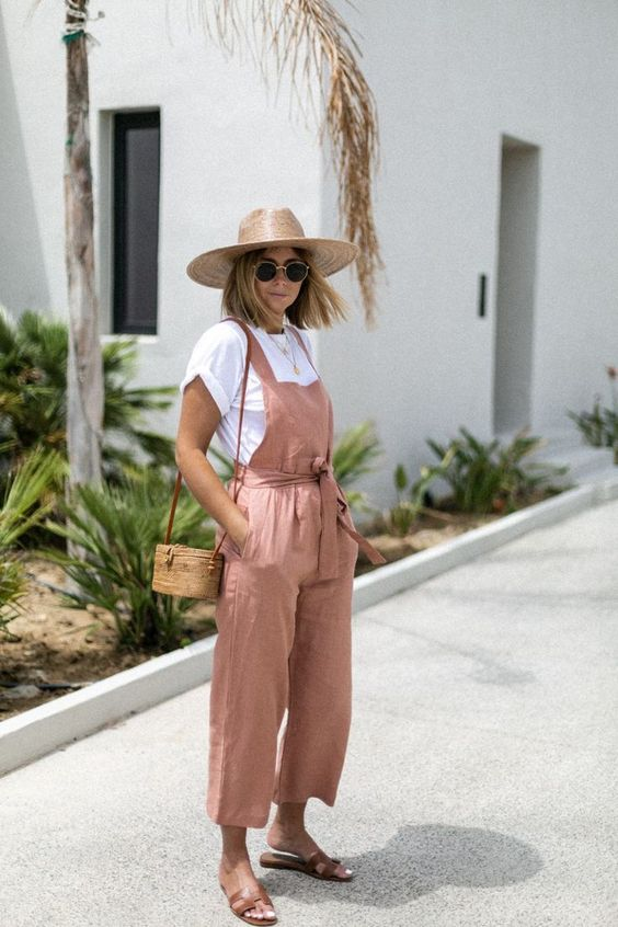 a breezy vacation look with a white tee, a mauve linen overall, brown slippers, a woven bag and a hat