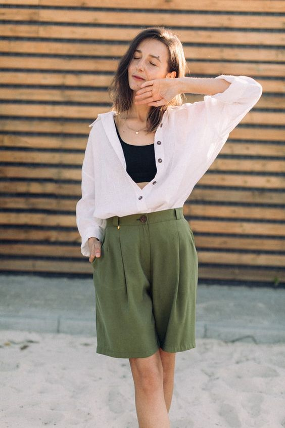 a casual summer outfit with a black crop top, a white shirt, army green Bermudas is comfy