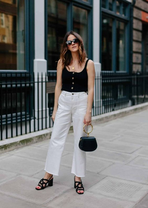 a chic look with a black button up top, white jeans, black block heels and a black bag with a ring handle