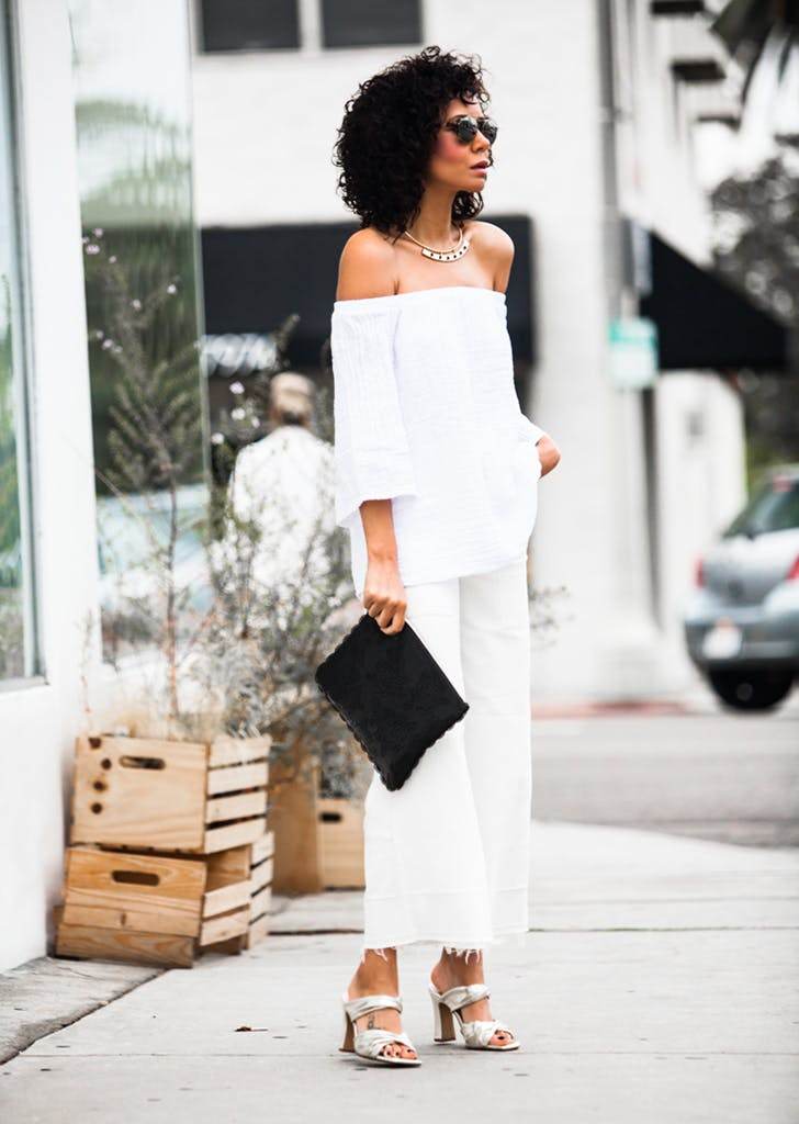 a chic outfit with a white off the shoulder top, white jeans, catchy heels and a black bag