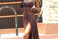 a chocolate brown polka dot midi dress with a thigh high slit, white sneakers, layered necklaces and a black bag