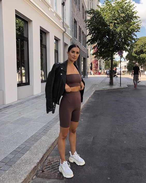 a chocolate brown suit of a crop top and biker shorts, a black leather jacket and white trainers