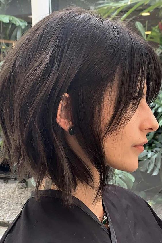 a choppy dark brunette bob with bangs and slight waves is a bold and chic idea