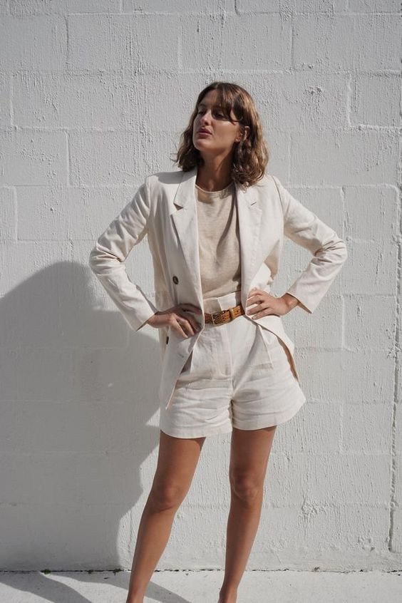 a classy look with a neutral top and a white linen short suit plus a brown belt is an ultimately elegant look