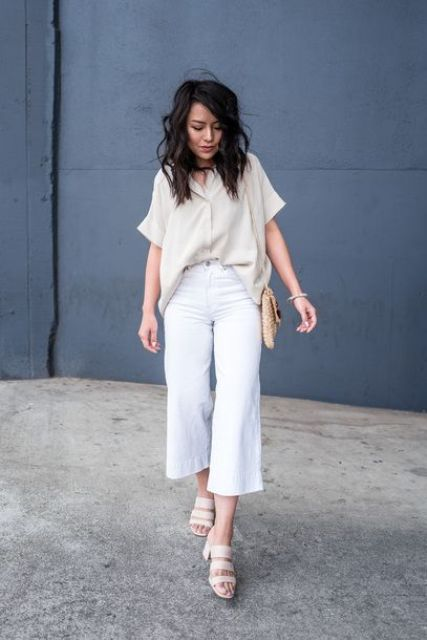 a cool linen work outfit with a loose neutral shirt with short sleeves, white cropped linen pants, neutral heels and a bag