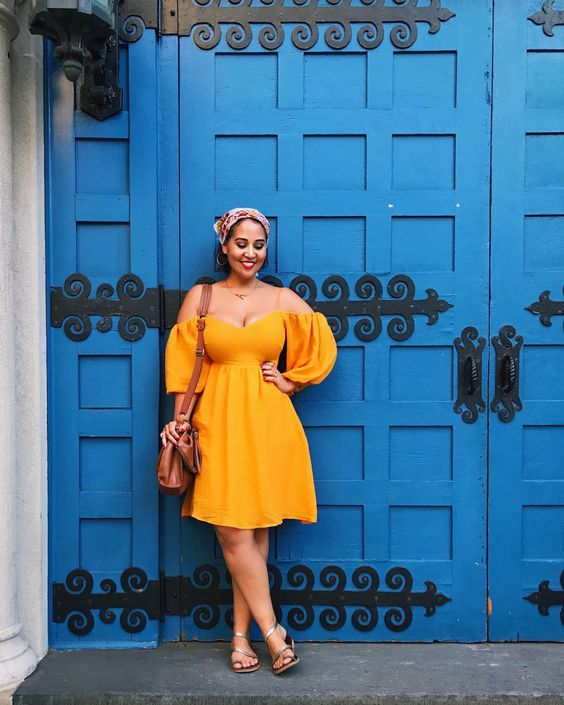 a cool off the shoulder yellow knee dress with puff sleeves, metallic sandals and a brown bag