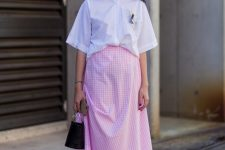 a crispy white blouse with short sleeves, a pink gingham midi, black heels and a bucket bag for a cute look