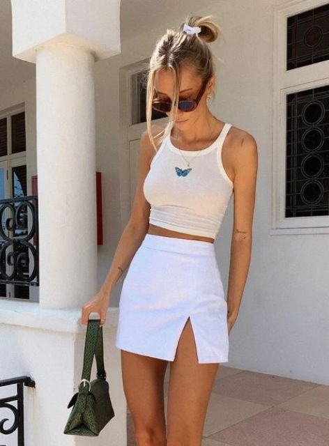 a crop top with a butterfly and a white A-line mini skirt with a slit plus a green bag for a hot day
