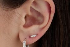 a delicate yet bold solution of a lobe piercing and a love orbital piercing done with chic diamond earrings