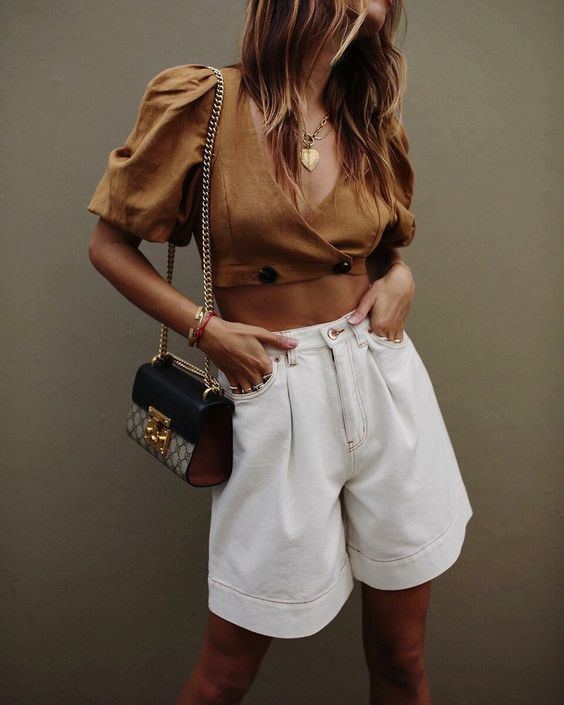 a fashionable outfit with a rust-colored cropped blouse with puff sleeves, white Bermudas, a two tone bag is wow