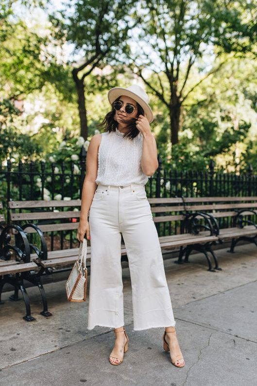 a feminine look with a boho lace sleeveless top, white wideleg jeans, nude heels, a beaded bag and a hat
