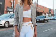 a glam look with a white crop top, white biker shorts, a plaid oversized blazer and layered necklaces plus a mini bag