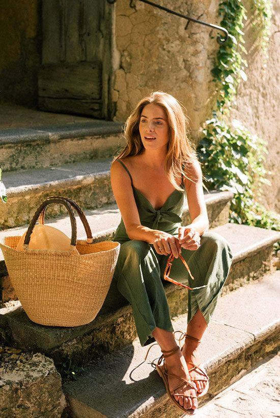 a green linen jumpsuit with wideleg pants and spaghetti straps, nude lace up shoes and a woven bag for a hot day