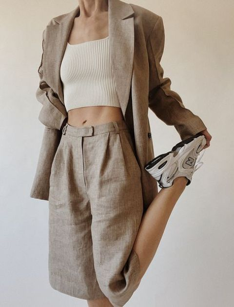 a grey linen suit with an oversized blazer and long Bermudas, a neutral crop top and neutral trainers