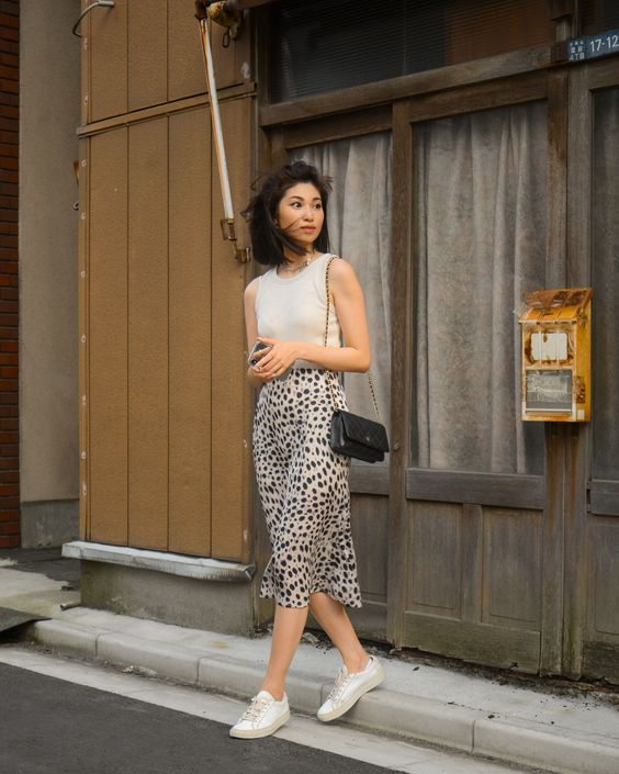 a grey sleeveless top, a Dolmatine print slip midi, white sneakers and a black bag compose a breezy summer outfit