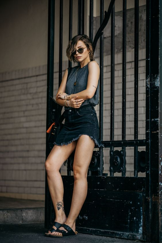 a grey sleeveless top, a black denim mini with fringe, black birkenstocks and a black bag for a sexy look