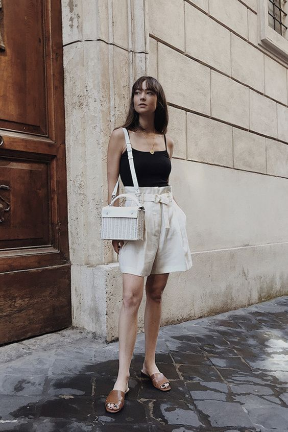 a hot day outfit with a black spaghetti strap top, neutral high waisted linen Bermudas, brown slippers and a neutral woven bag
