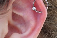 a lobe piercing paired with an orbital one, with a heart stud earring and a ring with a rhinestone are cool and bold