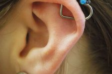a lobe piercing paired with an orbital one, with a large diamond stud and a heart-shaped earring with colorful rhinestones