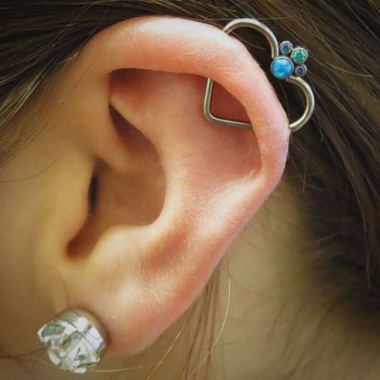a lobe piercing paired with an orbital one, with a large diamond stud and a heart shaped earring with colorful rhinestones