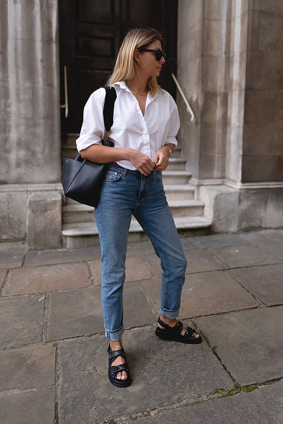 a lovely casual work look with a white shirt, blue jeans, black dad sandals, a black bag and a necklace is cool for summer