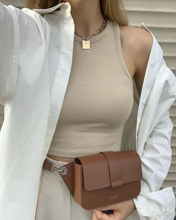 a modern minimalist look with a tan crop top, neutral high waisted trousers, a white shirt, a brown belt bag