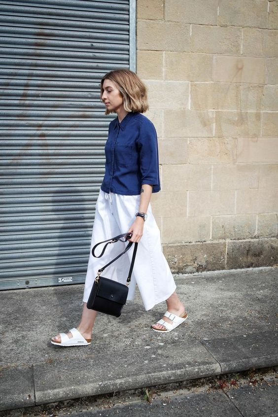 a navy cropped shirt with short sleeves, white culottes, white birkenstocks and a black bag create a cool summer work look