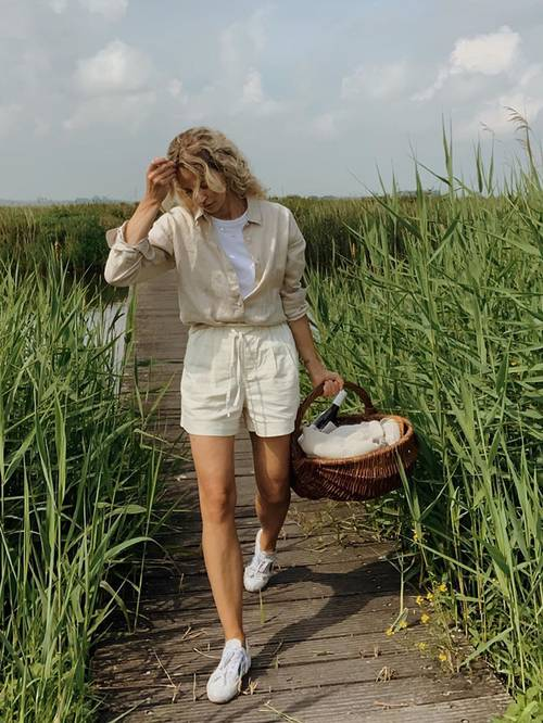 a neutral linen shirt and a white t-shirt, neutral linen shorts, white sneakers, a basket for a picnic are lovely