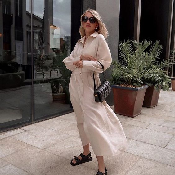 a neutral maxi shirtdress with long sleeves, a black bag and black dad sandals for a super chic and bold summer look