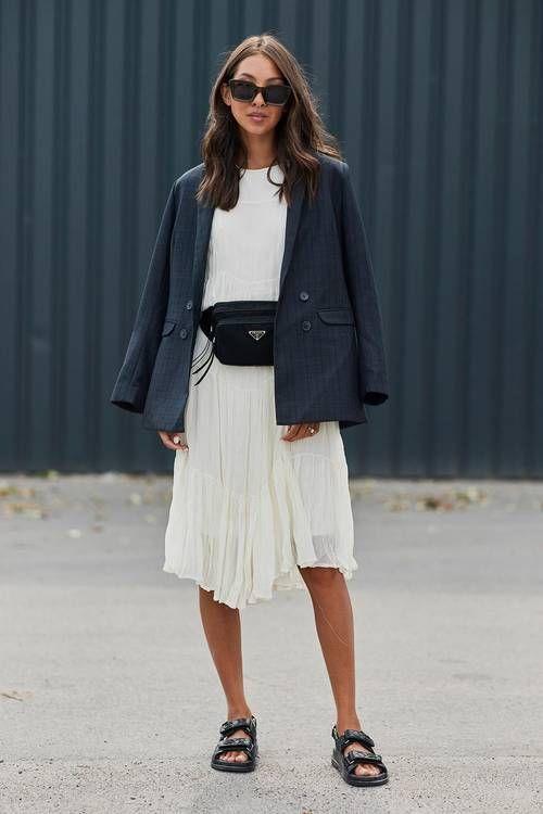 a neutral midi dress with an asymmetrical skirt, black dad sandals, a navy blazer and a black belt bag for an elegant work look