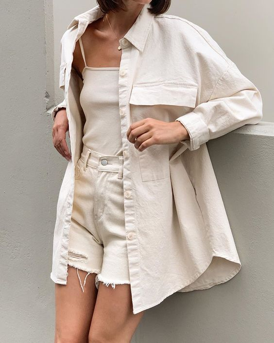 a neutral outfit with a top, ripped denim shorts, an oversized shirt for a lovely summer look