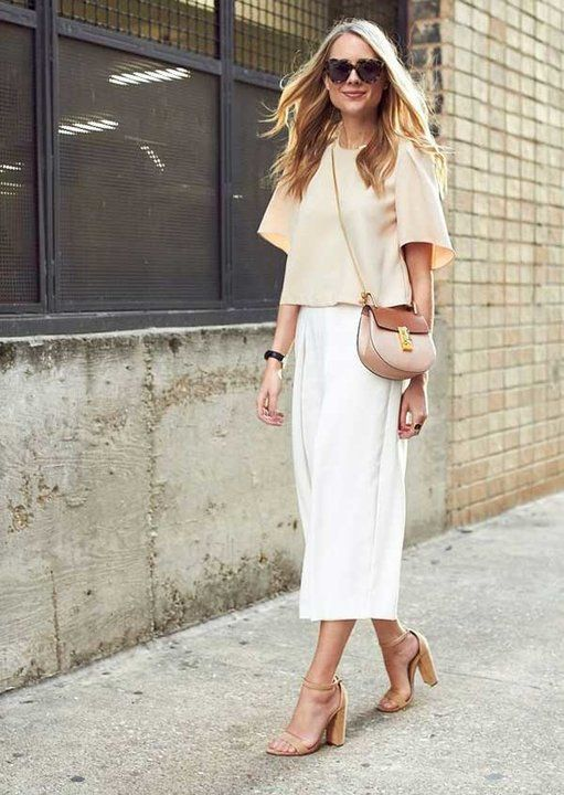 a neutral summer work look with a tan oversized top with short sleeves, white culottes, nude block heels and a two tone bag
