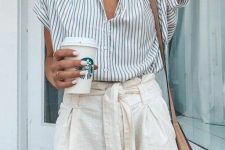 a pinstripe shirt with short sleeves, neutral linen shorts, a tan bag and layered necklaces for a hot working day