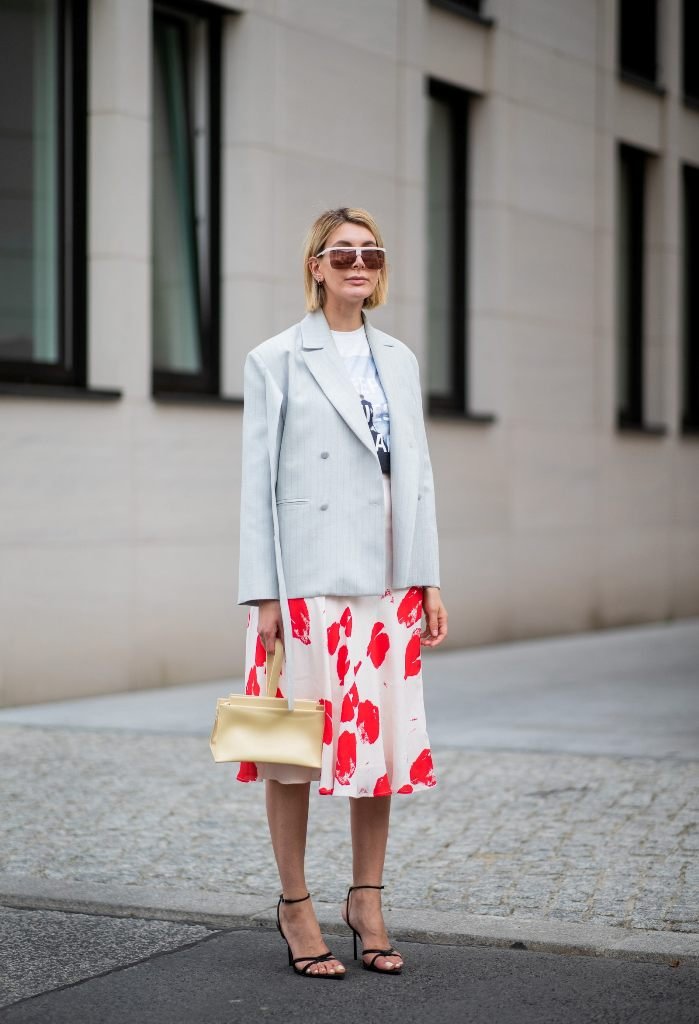 a printed t-shirt, a bold printed midi skirt, black strappy heels, a neutral bag and a pinstriped blazer for a cooler evening