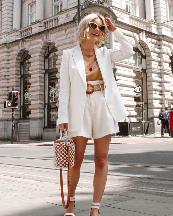 a refined work outfit with a white linen suitwith an oversized blazer, a nude top, white snakle strap heels and a bucket bag