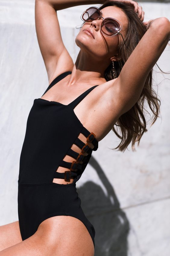 a retro-inspired black one piece swimsuit with cutout sides with buckles and thick straps looks elegant and very chic