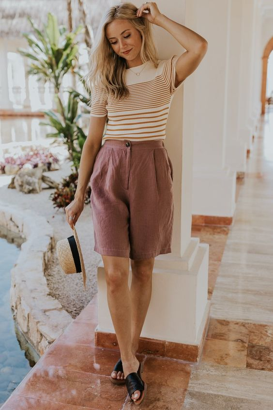 a retro vacation look with a striped top, mauve linen Bermudas, black slippers and a hat