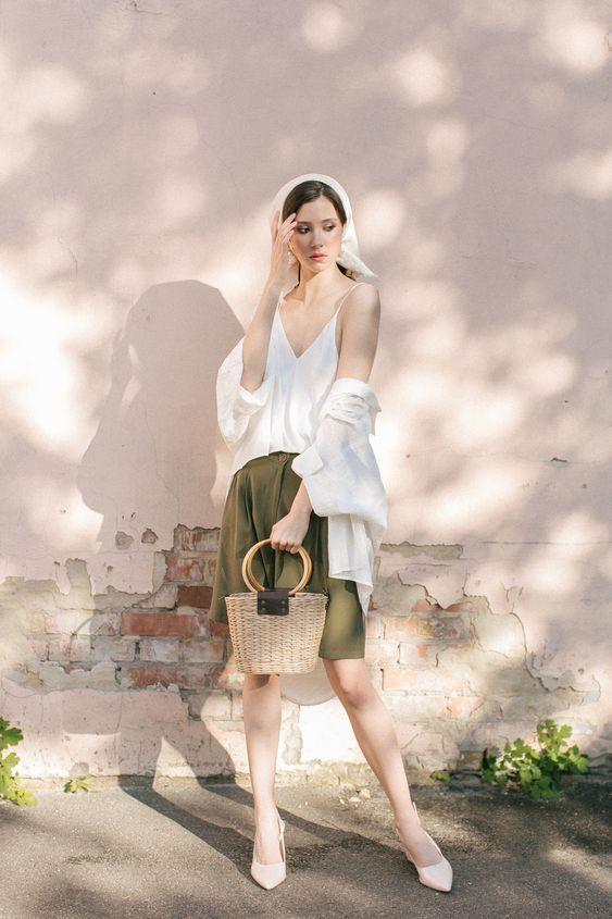 a romantic summer look with a white spaghetti strap top, green linen Bermudas, a white shirt, a head tie and a basket bag