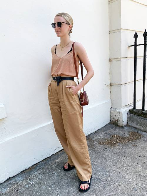 a rust-colored linen top, tan colored linen pants, black birkenstocks, a black belt and a brown bag are a hot day