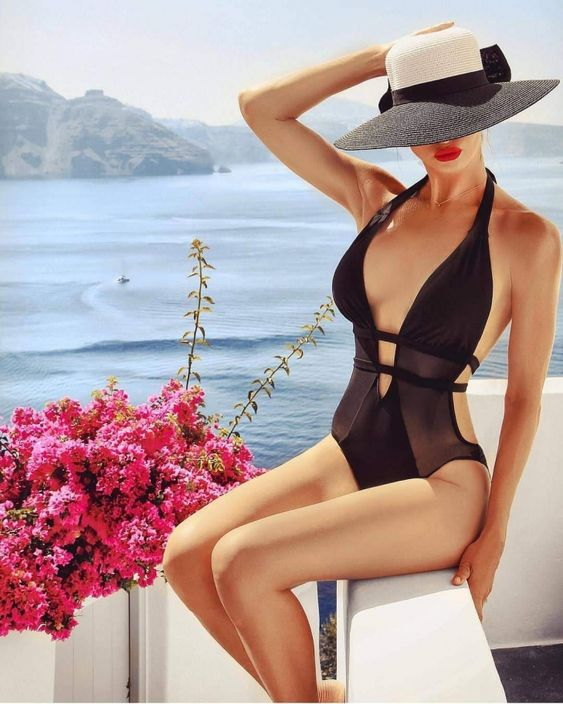 a sexy look with a black one piece side cutout swimsuit and a plunging neckline plus a vintage hat