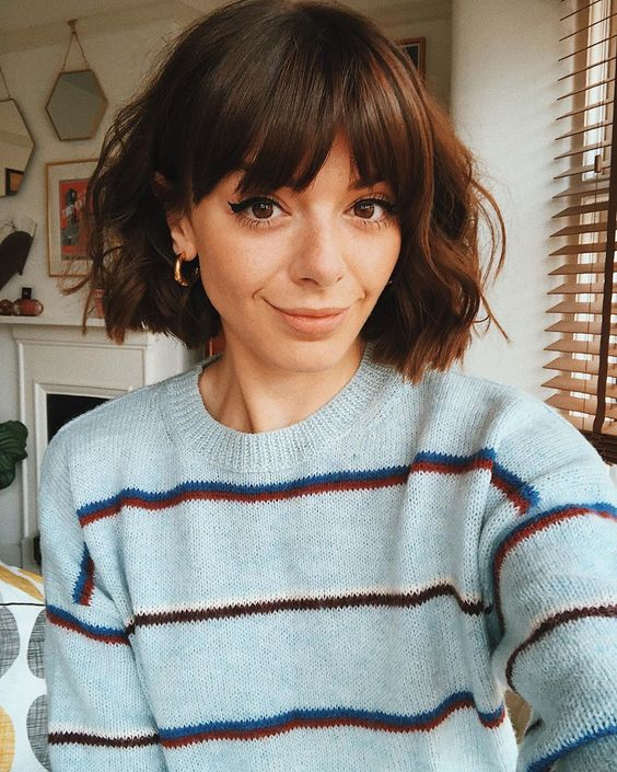 a short brunette bob with waves and bangs is a lovely and very girlish idea for any time