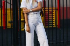 a simple and cool look with a white t-shirt, white jeans, a nude bag and pink velvet kitten heels for a touch of color