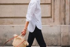 a simple look with a white shirt, black pants, printed birkenstocks and a straw bag is a cool idea