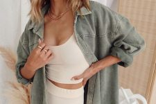 a simple summer look with a tan crop top and shorts plus a green denim shirt and layered necklaces