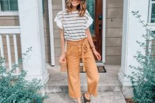 a striped t-shirt, tan paperbag waist cropped pants, black birkenstocks and a woven bag