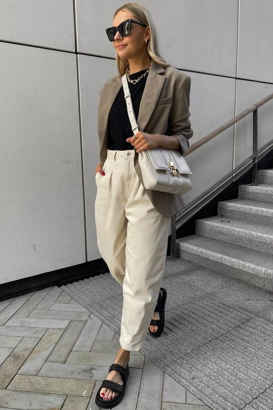 a stylish summer work outfit with a black top, creamy jeans, black dad sandals, a grey oversized blazer and a white bag