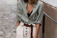 a summer look in natural colors – a black crop top, an olive green shirt, neutral high waisted pants and a straw bag