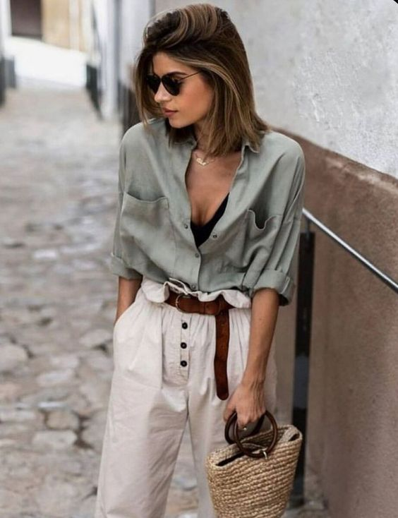 a summer look in natural colors - a black crop top, an olive green shirt, neutral high waisted pants and a straw bag